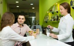 Weibliches barista und zwei Kunden im Café Lizenzfreies Stockbild