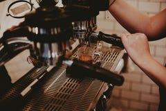 Weibliches barista unter Verwendung der Kaffeemaschine und -herstellung eines köstlichen Latte stockfotografie
