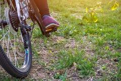 Weibliches Bein auf dem Pedal des Fahrrades Stockbilder