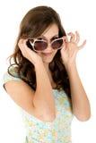 Weibliches Blicken des hübschen Brunette über ihrer Sonnenbrille Stockfotos