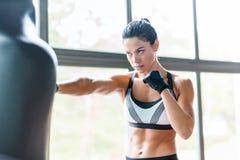 Weibliches Boxer-Training mit Sandsack lizenzfreie stockbilder