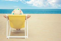 Weibliches Bräunen auf dem Strand, dem tragenden Strohhut, schönes Meerblick-, Reise- und Tourismuskonzept genießend Lizenzfreies Stockfoto