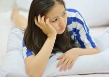 Weibliches Denken beim auf dem Bett zu Hause liegen Lizenzfreie Stockfotografie
