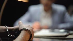 Weibliches Detektivschreibenszeugnis von zurückgehalten, Hände in der Handschellennahaufnahme stock footage
