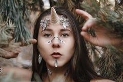 Weibliches Einhorn Feenhaftes Mädcheneinhorn, das auf den Schnee im Wald geht lizenzfreies stockfoto