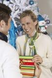 Weibliches empfangendes Weihnachtsgeschenk vom Mann Stockbilder