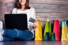 Weibliches erwachsenes lächelndes Kaufen der Frau, das Zahlung auf Modestoffinternet-Online-Shop-Geschäft durch Kreditdebitkarte  stockbild
