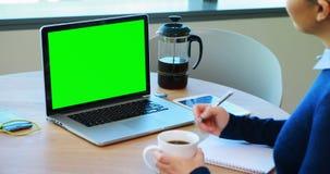 Weibliches Exekutivarbeiten über Laptop stock video footage