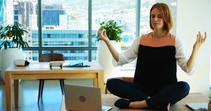 Weibliches Exekutivmeditieren an ihrem Schreibtisch stock video footage