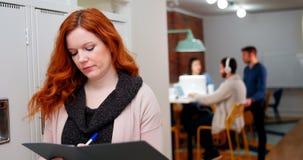 Weibliches Exekutivschreiben in der Datei im Umkleideraum stock video footage
