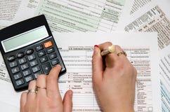 Weibliches füllendes Steuerformular 1040 Stockfotos