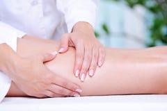 Weibliches Fahrwerkbein, das Massage durch Beautician erhält Lizenzfreie Stockbilder
