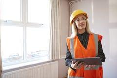 Weibliches Feldmesser In Hard Hat und hohe Sicht-Jacke mit Digital-Tablet-Durchführungshaus-Inspektion lizenzfreie stockfotografie