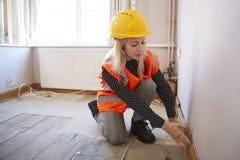 Weibliches Feldmesser In Hard Hat und hohe Sicht-Jacken-Durchführungshaus-Inspektion stockbild