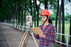 Weibliches Feldmesser oder Ingenieur, die Maß auf dem Feld machen Stockfotografie