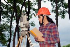 Weibliches Feldmesser oder Ingenieur, die Maß auf dem Feld machen Lizenzfreie Stockbilder