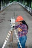 Weibliches Feldmesser oder Ingenieur, die Maß auf dem Feld machen Stockfoto