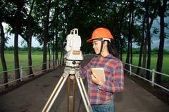 Weibliches Feldmesser oder Ingenieur, die Maß auf dem Feld machen Lizenzfreie Stockfotografie