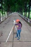 Weibliches Feldmesser oder Ingenieur, die Maß auf dem Feld machen Lizenzfreie Stockfotos