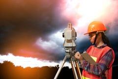 Weibliches Feldmesser oder Ingenieur, die Maß durch Theodolit auf dem Feld machen Lizenzfreies Stockfoto