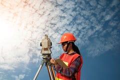 Weibliches Feldmesser oder Ingenieur, die Maß durch Theodolit auf dem Feld machen Lizenzfreie Stockfotografie