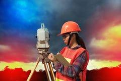 Weibliches Feldmesser oder Ingenieur, die Maß durch Theodolit auf dem Feld machen Stockbild