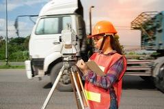 Weibliches Feldmesser oder Ingenieur, die Maß durch Theodolit auf dem Feld machen Stockfotografie