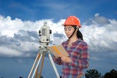 Weibliches Feldmesser oder Ingenieur, die Maß durch Theodolit auf dem Feld machen Stockfoto