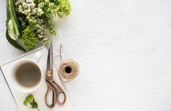 Weibliches flatlay mit Blumen und ccoffee auf weißer Tischplatte stockfotografie