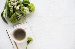 Weibliches flatlay mit Blumen und ccoffee auf weißer Tischplatte stockfotos