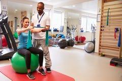 Weibliches geduldiges Arbeiten mit Physiotherapeuten In Hospital Stockfotos