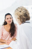 Weibliches geduldiges Hören auf Doktor mit Konzentration Stockbild