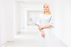 Weibliches geduldiges tragendes Krankenhauskleid und Aufstellung in einem Krankenhaus Stockfotografie