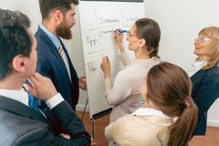 Weibliches Geschäftsführerschreiben auf einem Karton das Positiv stockbilder