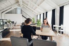 Weibliches Geschäftsteam, das eine Sitzung zusammen, zum der Schreibarbeit zu besprechen sitzt an einem Tisch hat eine Diskussion Lizenzfreie Stockfotos