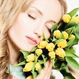 Weibliches Gesicht und Gelb Tulip Flowers Getrennt auf Weiß Lizenzfreie Stockfotos