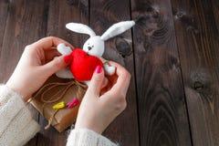 Weibliches haltenes Spielzeughäschen mit rotem Herzen Stockfoto