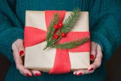 Weibliches haltenes Weihnachtsgeschenk im Kraftpapier mit rotem Leinwandband mit Dekor Lokalisierung auf Weiß Abschluss oben Froh Stockfotografie