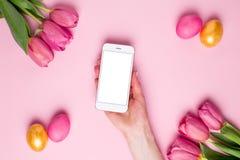 Weibliches Handgrifftelefon auf einem rosa Hintergrund mit Blumen und Ostereiern stockfotografie