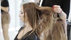 Weibliches Handtrockner das lange Haar eines jungen Mädchens mit einem Haartrockner im Schönheitsstudio stock video