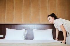 weibliches Haushaltungsarbeitskraftmädchen, das Bett mit Bettzeug am Gasthausraum macht Made Bett im Raum machend Lizenzfreies Stockbild