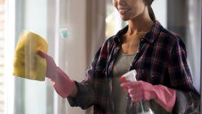 Weibliches Hotelmädchen in den Handschuhen, die Glasfenster nach Spray, Fleckentfernen abwischen Lizenzfreie Stockfotografie