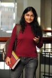 Weibliches indisches Kursteilnehmer-Holding-Mobiltelefon Stockfoto