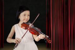 Weibliches Kind, das eine Violine auf Stadium spielt lizenzfreie stockfotografie