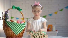 Weibliches Kind, das farbige Eier zählt und in Korb, glücklicher Ostern-Gruß sich setzt stock footage