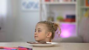 Weibliches Kind, das geheim Schokolade von der weißen Platte auf Tabelle, Zuckerüberdosis nimmt stock video footage