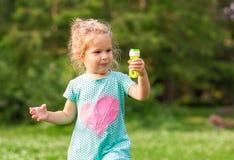 Weibliches Kind im Park mit Seifenblasen Lizenzfreies Stockfoto