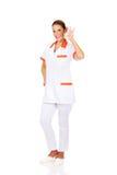 Weibliches Krankenschwester- oder Doktorgestikulieren des Jungelächelns Stockfoto