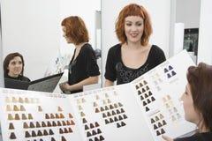 Weibliches Kunden-und Friseur-Looking At Color-Diagramm Stockfoto