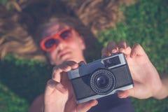 Weibliches Lügen im Gras und Machen des Fotos mit Retro- Kamera Stockfotografie